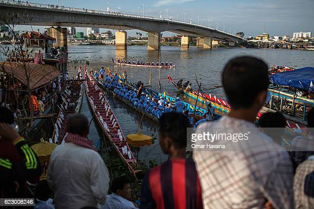 People gather to watch boat crew members training on the waters of the Tonle Sap River on the morning of the first day of the Water Festival on...