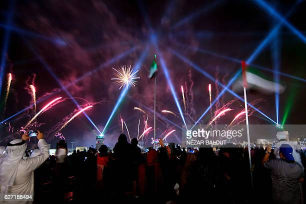 People gather to watch fireworks and water attractions marking the United Arab Emirates 45th National Day celebrations in Abu Dhabi on December 2...