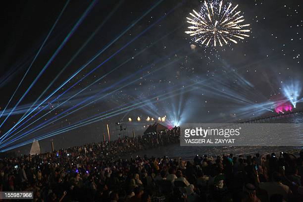 People gather to watch fireworks as they light the sky near the Kuwait Towers during celebrations marking the Gulf state's 50th anniversary of its...
