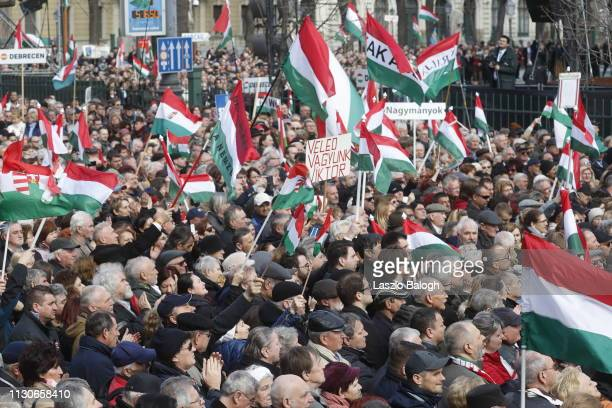 People gather to watch Hungarian Prime Minister Viktor Orban deliver a speech in front of the National Museum during Hungary's National Day...