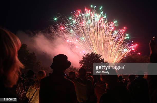 People gather to watch the fireworks display launched above the stone circle at the Glastonbury Festival of Contemporary Performing Arts site at...