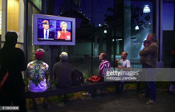 TOPSHOT People gather to watch the first US presidential debate between Hillary Clinton and Donald Trumpnominees for the Democratic and Republican...