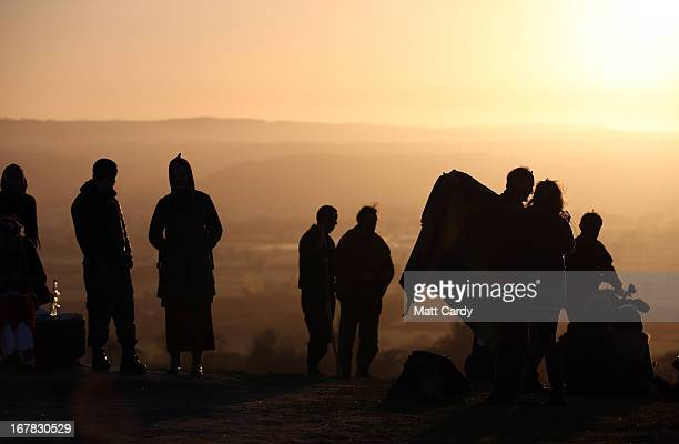 People gather to watch the sun rise as they join in a Beltane dawn celebration service in front of St Michael's Tower on Glastonbury Tor on May 1...