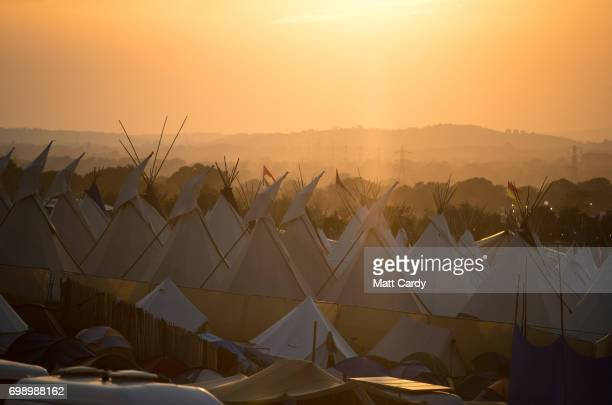 People gather to watch the sun set ahead of the gates opening to the public amid heightened security this year at the Glastonbury Festival site at...
