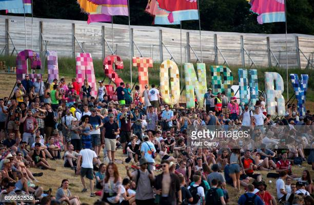 People gather to watch the sun set as temperatures reach record levels at the Glastonbury Festival at Worthy Farm in Pilton on June 21 2017 near...