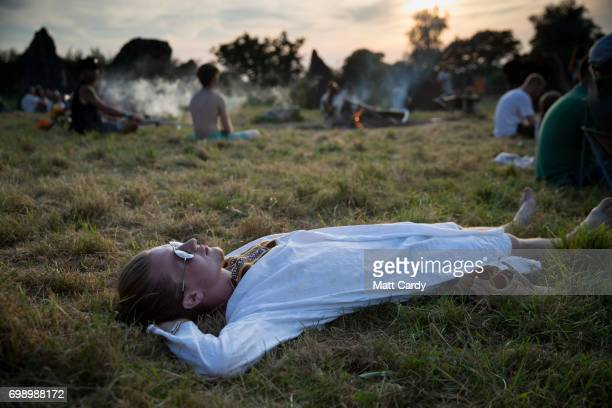 People gather to watch the sun set at the Stone Circle ahead of the gates opening to the public amid heightened security this year at the Glastonbury...