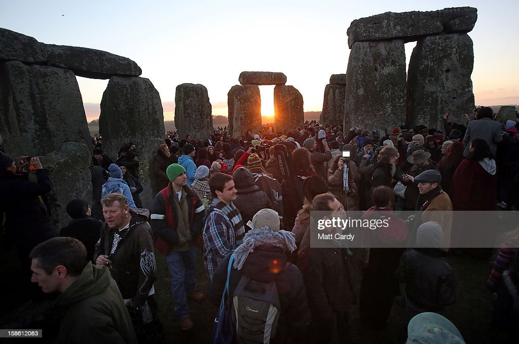 People gather to watch the sunrise as druids, pagans and revellers celebrate the winter solstice at Stonehenge on December 21, 2012 in Wiltshire, England. Predictions that the world will end today as it marks the end of a 5,125-year-long cycle in the ancient Maya calendar, encouraged a larger than normal crowd to gather at the famous historic stone circle to celebrate the sunrise closest to the Winter Solstice, the shortest day of the year.