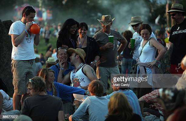 People gather to watch the sunset at the stone circle as music fans start to arrive at the Glastonbury Festival site at Worthy Farm, Pilton on June...