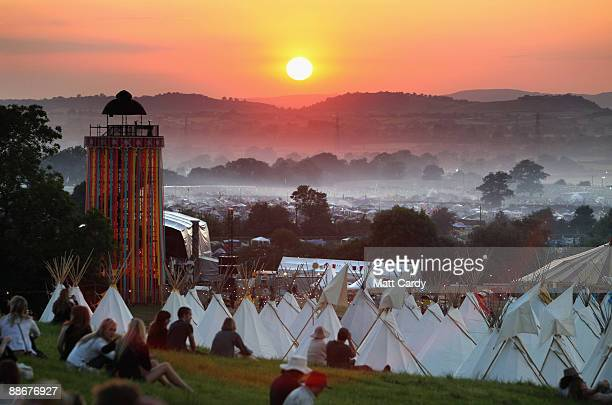 People gather to watch the sunset on a hill above the tipi field as music fans start to arrive at the Glastonbury Festival site at Worthy Farm Pilton...