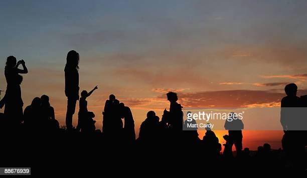 People gather to watch the sunset on a hill above the tipi field as music fans start to arrive at the Glastonbury Festival site at Worthy Farm,...