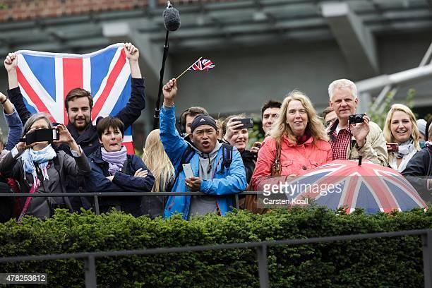 People gather to wave to German President Joachim Gauck, his partner Daniela Schadt, Queen Elizabeth II and Prince Philip, the Duke of Edinburgh, as...