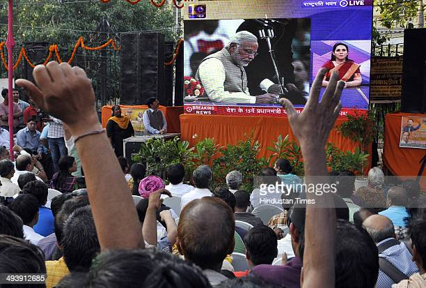 People gather to witness live telecast of swearingin ceremony of Narendra Modi as as 15th Prime Minister of India on huge TV screen at Chandini Chowk...