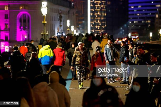 People gather together on Westminster Bridge in London, late on New Year's Eve, December 31 despite the message to stay at home in the Tier 4 city...