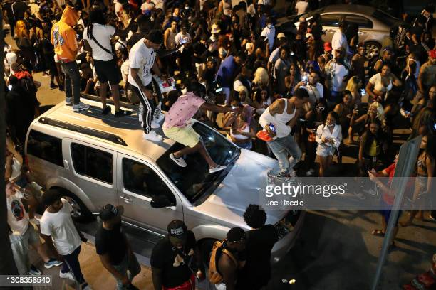 People gather while exiting the area as an 8pm curfew goes into effect on March 21, 2021 in Miami Beach, Florida. College students have arrived in...