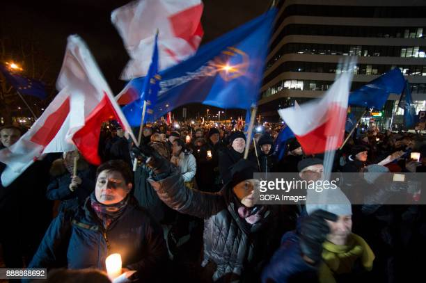 People gather while holding flags in front of Krakow Court to protest against the new judicial reforms Today The Polish parliament approved the...