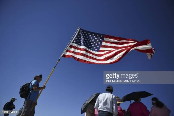 People gather with a flag at the Tornillo Port of Entry near El Paso Texas June 21 2018 during a protest rally including several American mayors...