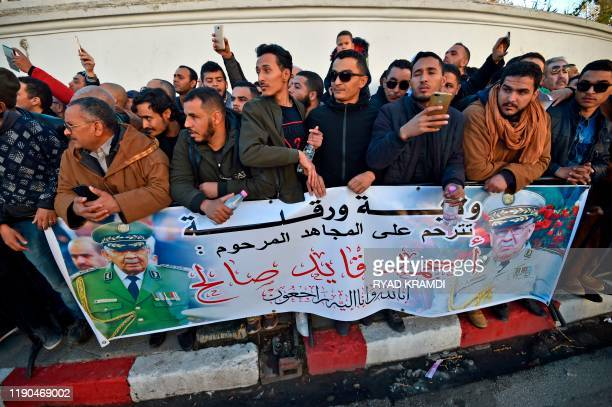 People gather with a mourning sign outside the Palais du Peuple during the funeral of Algeria's late military chief Lieutenant general Ahmed Gaid...