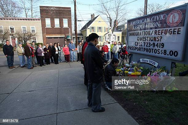 People gather with flowers in front of the American Civic Association to pay their respects to the 13 victims of a recent mass shooting April 5, 2009...