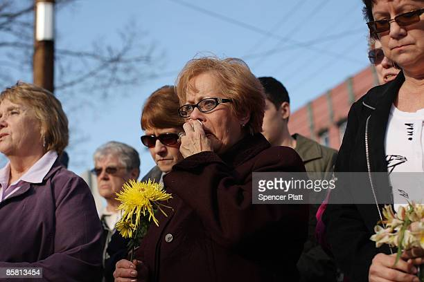 People gather with flowers in front of the American Civil Association to pay their respects to the 13 victims of a recent mass shooting April 5, 2009...