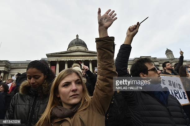People gather with signs and pencils held aloft in Trafalgar Square in central London on January 11 2015 to commemorate the victims of the attacks in...