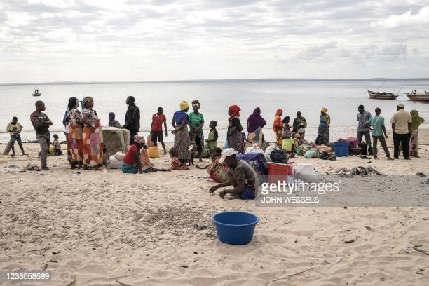 People gather with their belongings as they arrive at Paquitequete beach in Pemba on May 22 after fleeing Palma by boat. - The Paquitequete beach in...