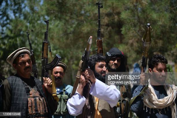 People gather with their heavy weapons to support Afghanistan security forces against the Taliban, in Guzara district, Herat province on June 23,...