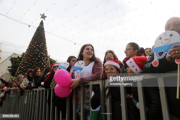 People gather within the 'Jerusalem is Capital of Palestine' themed Christmas celebrations at Manger Square in Bethlehem West Bank on December 24...