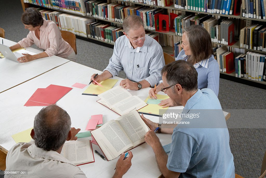 People gathered around table in library, elevated view : Foto de stock