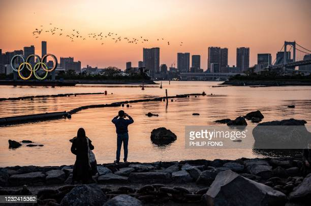 People gathered as the Olympic rings are lit at the waterfront of Odaiba in Tokyo on April 20, 2021.