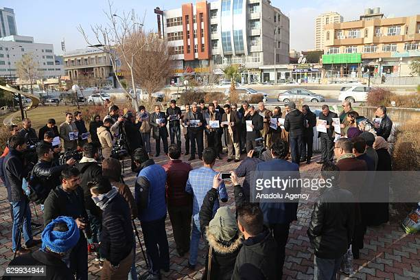 People gathered at Nali Park hold pictures as they take part in a protest against Assad regime forces' and its supporters' attacks on civilians and...