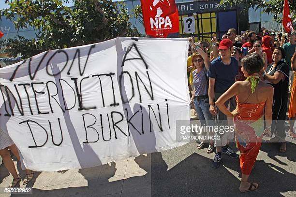 People gathered for New AntiCapitalist Party summer meeting hold a banner reading Against forbidding the wearing of the burkini as they march in...