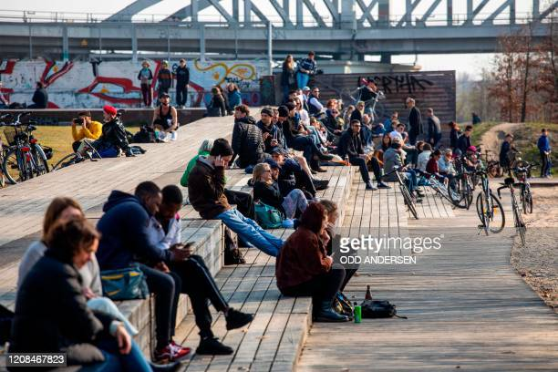 People gathered in Gleisdreieck park listens to patrolling police officers using a tannoy and screens mounted on a police van to address them in...