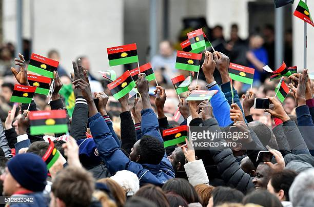 People gathered in St Peter's square at Vatican shake Biafra's flag as they listen to Pope Francis' weekly general sunday audience on February 28...