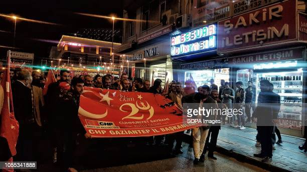 People gathered on Independence Day in the city of Gaziantep while holding a large banner and march down the street during the night time