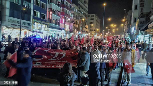 People gathered on Independence Day in the city of Gaziantep while holding a large banner and marching down the street at nighttime
