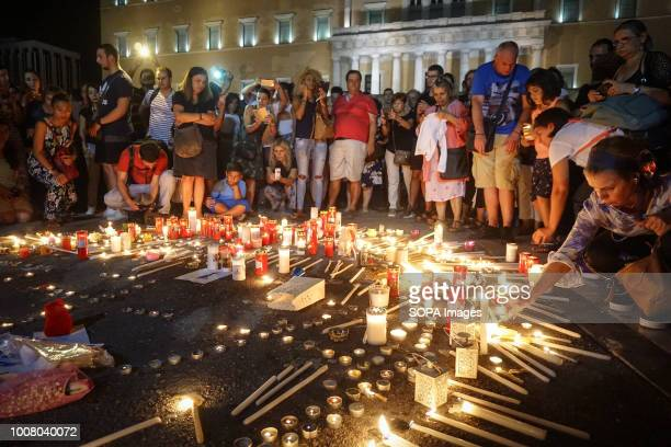 People gathered outside the Hellenic Parliament in memory of the 91 victims of the deadly fire in Eastern Attica as they symbolically formed with...