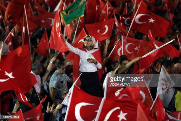 Waving the national flag people gather outside the Turkish parliament or Grand National Assembly as they attend the July 15 Democracy and National...
