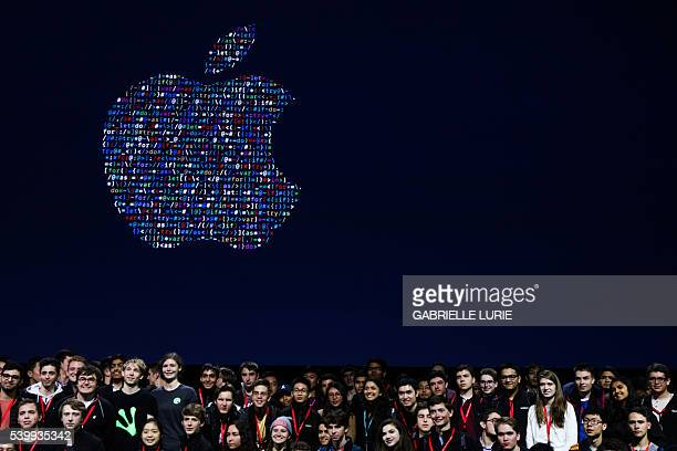 People gathered together to take a group photo with Apple's logo at Apple's annual Worldwide Developers Conference at the Bill Graham Civic...