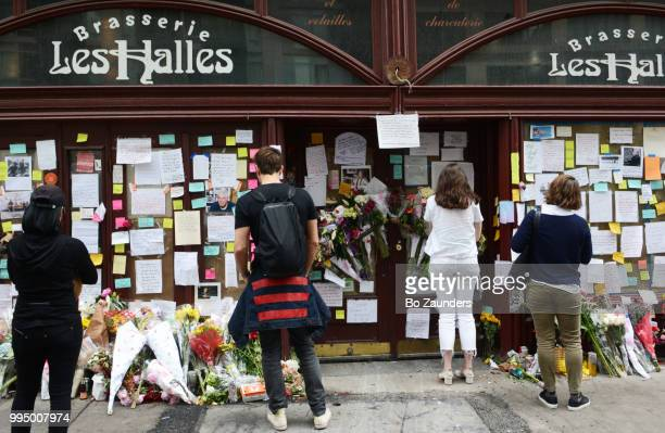People gathering in front of flowers, notes, and photos left in memory of Anthony Bourdain, at the closed location of Brasserie Les Halles in NYC, where Bourdain once worked as the executive chef.