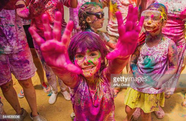 People gathering together celebrating a Holi party in the outdoor with happiness expressions and covered with vivid colors.