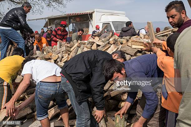 People gathers fire wood from a pile and moving them quickly to their tents in Idomeni Greece on 1st April 2016 The life in the camp is getting...