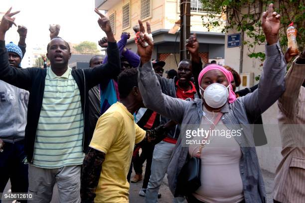 People gesture and cover their faces as Senegalese policemen fire tear gas during anti-government demonstrations in Dakar on April 19, 2018. -...