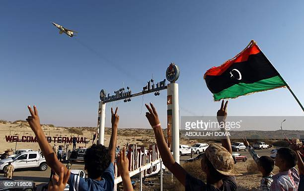 People gesture and wave a Libyan flag as fighter jet flies by at the Zueitina oil terminal on September 14 2016 Forces opposed to Libya's unity...