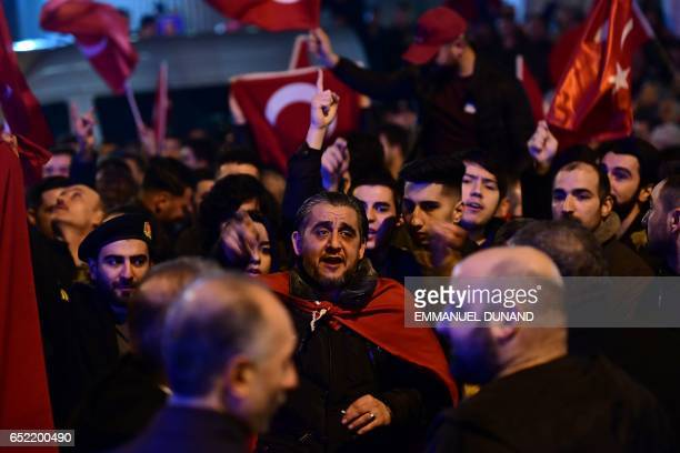 People gesture and wave flags as Turkish residents of the Netherlands gather for a protest outside Turkey's consulate in Rotterdam on March 11 2017...