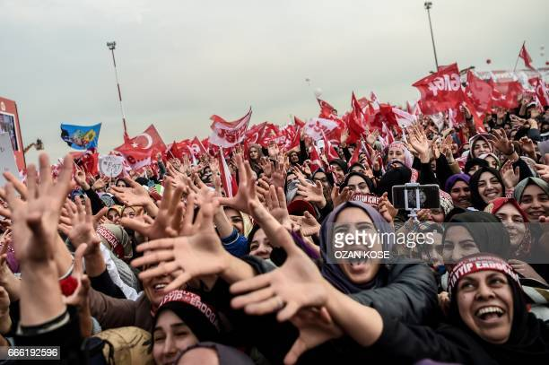 TOPSHOT People gesture and wave 'YES' banners and Turkish national flags as they shout on April 8 2017 during a campaign rally for the 'yes' vote in...