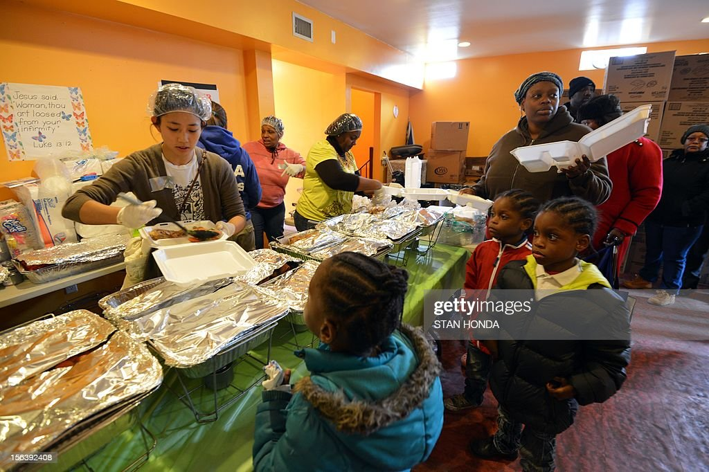 People get a hot meal at the Community Church of the Nazarene in the Far Rockaway section of Queens November 14, 2012 in New York as the city recovers from the effects of super storm Sandy. The church has serve up to 1,000 meals a day to residents affected by the storm. AFP PHOTO/Stan HONDA