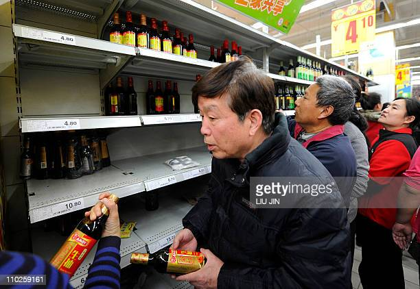 People get bottles of soy sauce which contains iodine from the supermarket after salt sold out due to panic buying in Beijing on March 17 2011...