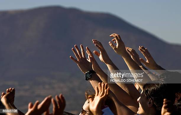 People get energy from the sun atop the Pyramid of the Sun in Teotihuacan Mexico during the celebrations for the Spring Equinox on March 21 2009...