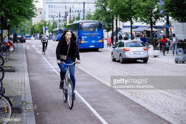 People get off a bus in the city centre of Lahti, where a pilot project is implemented to quantify the personal carbon footprint, on August 24, 2020....