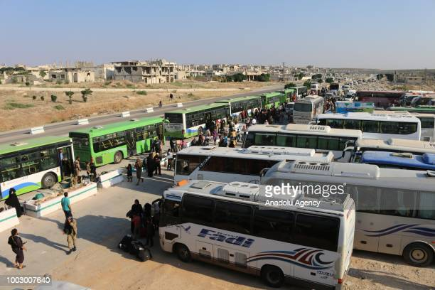 People get on buses headed towards temporary refugee centers in Idlib following the arrival of first evacuation convoy of 40 buses transporting 500...